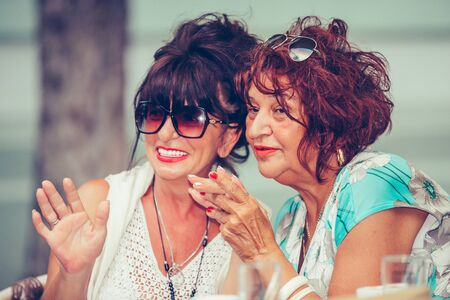 Image of a two happy senior women friends sitting in cafe talking with each other drinking coffee, pointing fingers to someone.