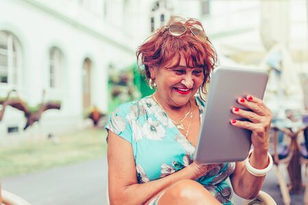Smiling senior woman spending time in a outdoor cafe using digital tablet. Attractive senior woman  laughing while reading electronic book via digital tablet. Stockfoto