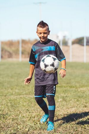Boy kicking football on the sports field during soccer training. Focus on the ball