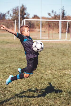 Taking the ball on the chest in football. Jumping little boy in action, movement at game. Junior football player is jumping to hitting soccer ball with chest. Sport action