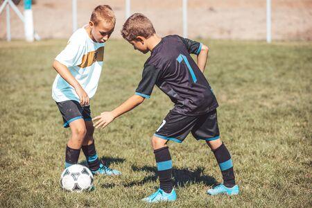 Boys in soccer jerseys kicking football on the sports field