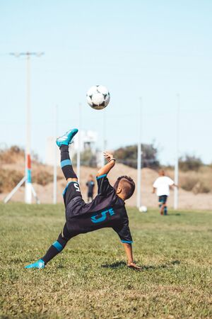 Little boy with soccer ball doing flying kick at stadium. Kid soccer player in motion on green grass background. Junior football player in action, jump, movement at game.