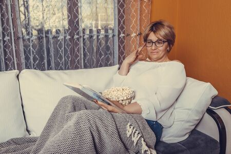 Middle aged woman reading book and eating popcorn while sitting on the couch at home Stockfoto