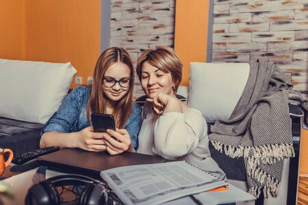 Portrait of beautiful smiling woman and her teenage daughter in jeans shirt using phone and watching funny video while sitting on the floor at home