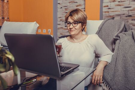 Beautiful middle aged woman working on laptop in the comfort of her living room.