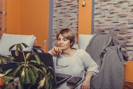Beautiful middle aged woman using laptop in the comfort of her living room. Stockfoto