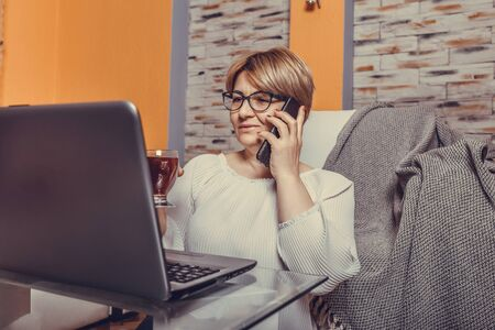 Beautiful middle aged woman talking on phone and working on laptop at home.
