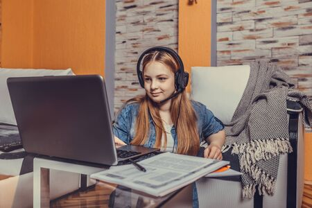 Happy teenage girl sitting on the floor wearing headphones greeting during a video call online with a laptop in the living room Stockfoto