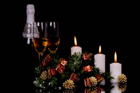 Two wine glasses with champagne, bottle, candles and Christmas ornaments on a black background with reflection. Copy space. Merry Christmas and Happy New Year, background