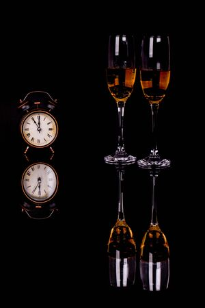 Two wine glasses with champagne and clock on a black background with reflection. Copy space. Merry Christmas and Happy New Year, background