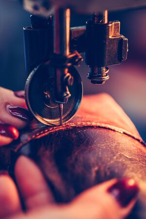 Hands of an experienced seamstress stitching a part of the shoe  in the handmade footwear industry