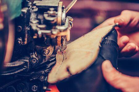 Hände eines erfahrenen Schuhmachers, der in einer Schuhfabrik einen Teil des Schuhs näht