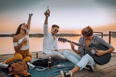 Happy friends playing the guitar and having fun on the beach in the sunset. Cheerful young people spending nice time together while sitting on the beach and drinking beer Imagens