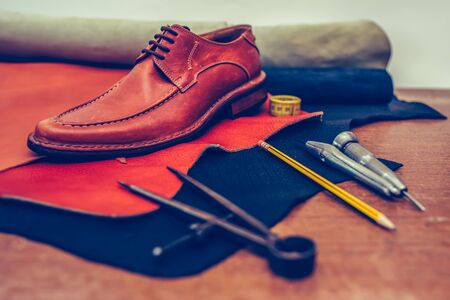 Shoemaker's work desk. Tools and leather at cobbler workplace. Man classic brown shoes and leather shoemaking tools and set of leather craft tools . Shoes maker tools on wooden table. Selective focus and small depth of field.