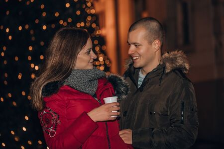 Young cheerful couple outdoors on a winter eve, with hot drinks, looking at each other, so tender, romantic, tempting, sensual. True love and feelings Banque d'images - 138286128