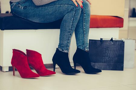 Cropped image of a middle aged woman trying on elegant shoes with high heels, while sitting in the shoe store