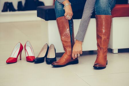 Cropped image of middle aged woman trying on deep boots, while sitting in a fashion store. Stock Photo