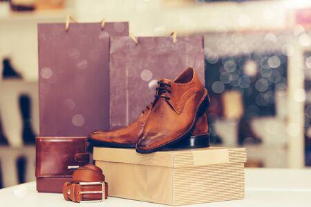 Nahaufnahme von eleganten Herrenlederschuhen, Gürtel, Brieftasche und Einkaufstaschen in einem Hintergrund auf dem Regal im Schuhgeschäft. Platz kopieren.