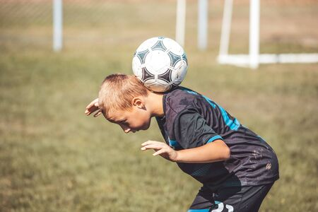 Young boy performs soccer ball exercises on the football field. Young soccer player showing skills with ball.