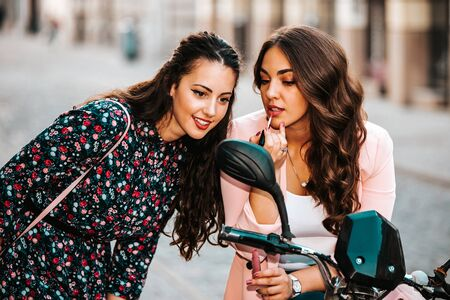 Two young beautiful women putting lipstick looking in mirror, while sitting on the scooter.