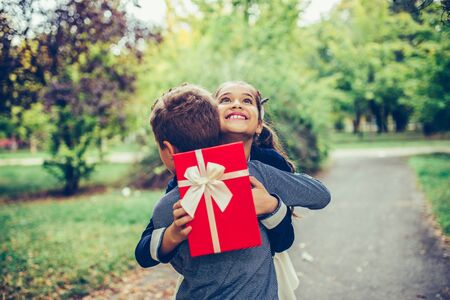Happy little child boy gives smiling girl a gift in a red box, making a surprise.