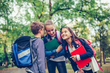 Three happy friends with backpacks laughing and having fun in the park. Boy and girl holding books on the first school day. Positive kids whispering a secret each other in the ears.