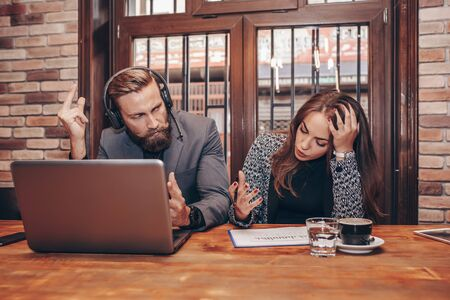Two sad and worried employees reading bad news together on line in a laptop. Man and woman working together on paper work and talking about reports and finance. Negative emotions, problems at work.