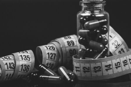 Closeup of a Glass bottle with diet pills and measuring tape isolated on black background. Black and white photo.