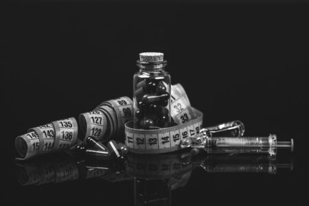 Closeup of a Glass bottle with diet pills, measuring tape syringe and medicine in ampoule. isolated on black background. - Image Foto de archivo