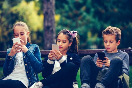 Group of friends playing video games on smart phone after school while sitting on the bench in the park.