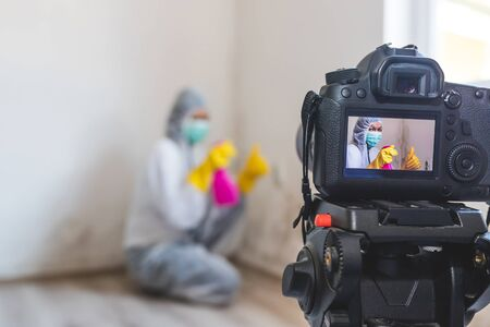 Close up of a video camera filming how woman cleaning mold from wall using spray bottle with mold remediation chemicals, mold removal products. A woman evaluates the product in a bottle excellent and gestures thumbs up. 写真素材