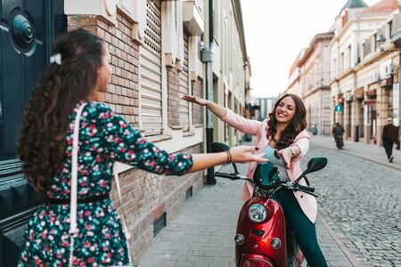 Woman waving friend. Two happy friends meeting and greeting in the street.