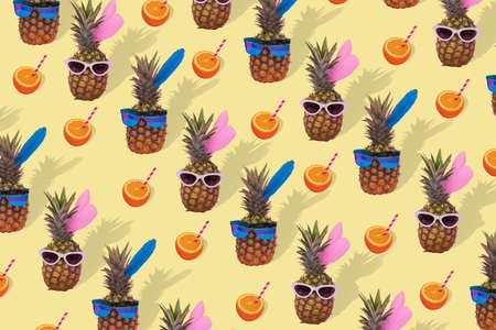 Fashion and trend. Female and male pineapple hipster in sunglasses, stylish fruit pattern on yellow background. Minimal concept, summer tropical pineapples with fresh orange juice. Creative art fashionable vacation concept. Stock Photo