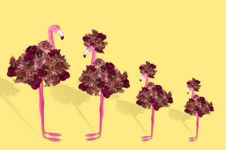 Creative fun concept with a stylized couple of flamingos and their children on illuminating yellow background. Minimal concept of happy family, vacation, parenting. Free space for text