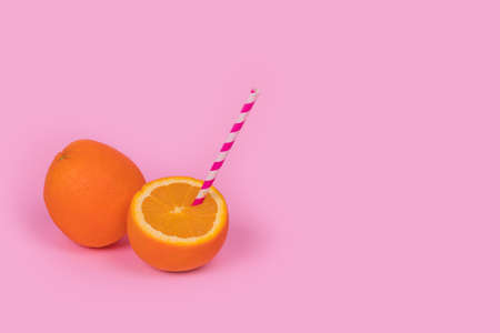 Minimal trendy idea with half an orange and a straw on pastel pink background. Pop art design with fresh fruit and refreshing drink. Creative summer party and vacation concept. Copy space Stock Photo