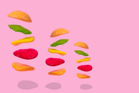 Flying Hamburger in layers, fast food on pastel pink background. Minimal junk food concept. Abstract creative food concept with gummy candies.