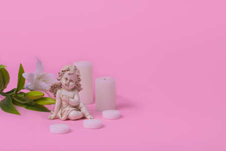 Minimal creative idea with a white angel, candles and a flower on a pink background. The concept of love, forgiveness, gratitude. Free space for text Stock Photo