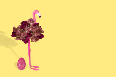 Creative fun idea with stylized flamingo and Easter pink egg on a illuminating yellow background. Minimal Easter and spring or summer Holiday concept. Free space for text