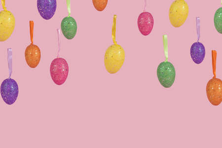 Creative Easter layout made of flying colorful eggs on light pink background. Minimal easter concept. Easter card with copy space for text.