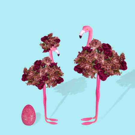 Creative idea with stylized couple of flamingo and Easter pink egg on a pastel blue background. Minimal spring or summer Holiday love concept. Free space for text