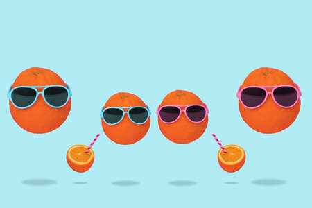 Orange party of fresh fruit, hipster in sunglasses with fresh orange juice, stylish fruit. Minimal concept of family time, vacation and summer. Creative art fashionable vacation concept. Summertime color mood.Fashion and trend. Copy space