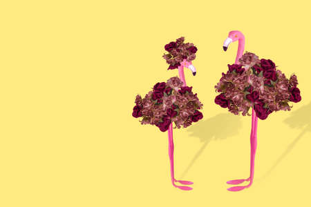 Creative fun concept with a stylized couple of flamingos on illuminating yellow background. Pattern with exotic flamingo. Minimal spring or summer Holiday love concept. Free space for text Stock Photo