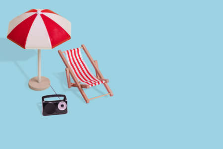 Creative minimal summer idea made of  sun umbrella, deck chair and radio on a light blue background. Modern concept of vacation, travel, fun and summer time. Copy space