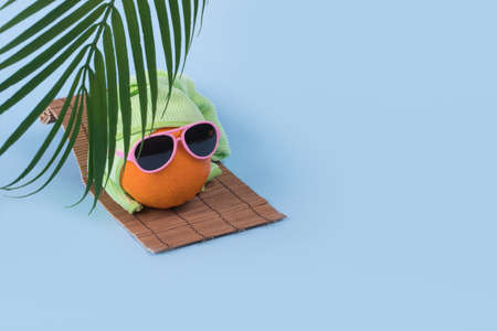 Fun idea made with an orange in sunglasses wearing a towel on his head lying on a sunbed and a palm leaf on a blue background. Trendy invitations with stylized fruit with space for text. Creative art, fashionable vacation, travel and fun concept. Stock Photo
