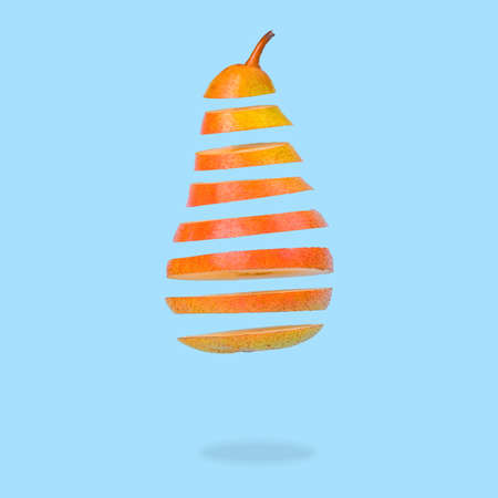Minimal idea with Floating levitating ripe pear on pastel blue background. Vitamins, healthy food concept. Sliced pear floating in the air. Creative concept with flying fruits. Stock Photo
