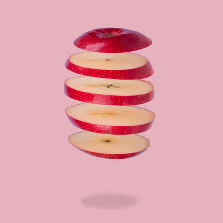 Floating levitating ripe apple on pink background. Vitamins, healthy diet concept. Minimal fruit idea. Sliced apple floating in the air. Creative concept with flying fruits.