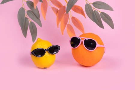 Orange and lemon fruit hipster in sunglasses on pastel pink background. Minimal travel concept, summer stylish tropical fruit. Creative art fashionable vacation concept. Summertime color mood.Fashion and trend. Stock Photo