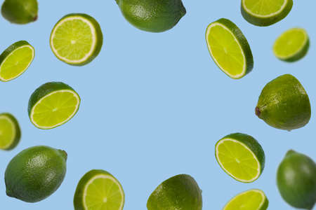 Falling limes isolated on a pastel blue background with space for text. Minimal fruit concept.Vitamins, healthy diet concept. Sliced lime floating in the air. Creative concept with flying fruits. Stock Photo