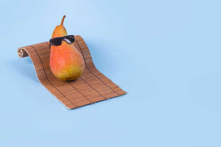 Minimal Fun idea made with a pear in sunglasses lying on a sunbed on a blue background. Trendy invitations with stylized fruit with space for text. Creative art, fashionable vacation, travel and fun concept.