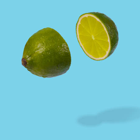 Minimal idea with fresh lime sliced on pastel blue background. Minimal fruit concept.Vitamins, healthy diet concept. Sliced lime floating in the air. Creative concept with flying fruits.